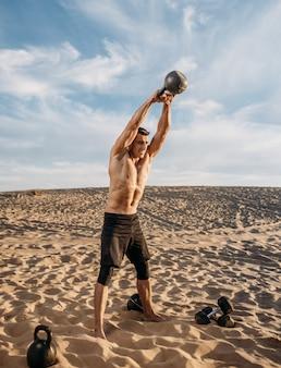 Muskulöser männlicher athlet mit kettlebell in der wüste