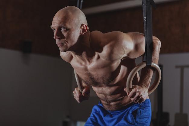 Muskulöser männlicher crossfit athlet, der auf gymnastischen ringen ausarbeitet