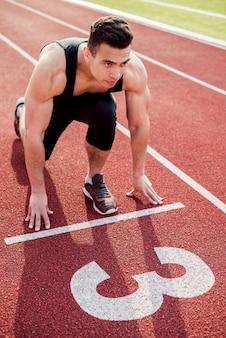 Muskulöser männlicher junger läufer auf der startlinie
