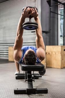 Muskulöser mann auf anhebendem dummkopf der bank an der crossfit turnhalle