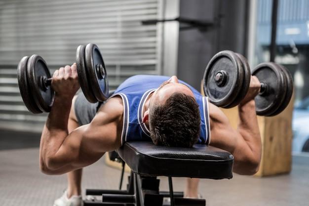 Muskulöser mann auf anhebenden dummköpfen der bank an der crossfit turnhalle