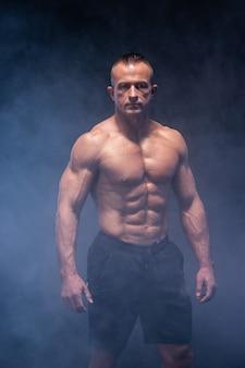 Muskulöser mann auf dem schwarzen hintergrund isoliert. starke männliche nackte oberkörper-bauchmuskeln.