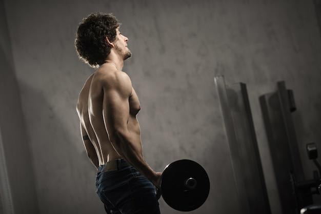 Muskulöser mann bildet bizeps mit barbell in der turnhalle, handtraining aus