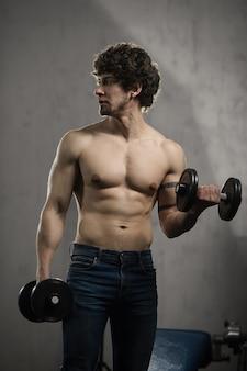 Muskulöser mann bildet bizepsdummköpfe in der turnhalle, handtraining aus