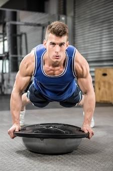 Muskulöser mann, den das handeln auf bosu ball an der crossfit turnhalle hochdrückt