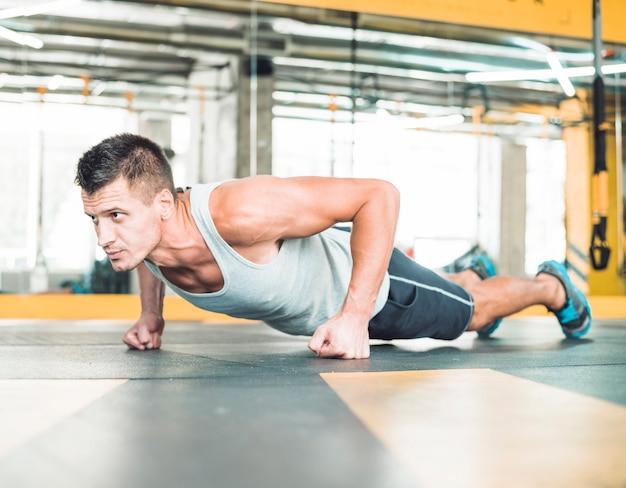 Muskulöser mann, den das handeln drückt, ups in turnhalle