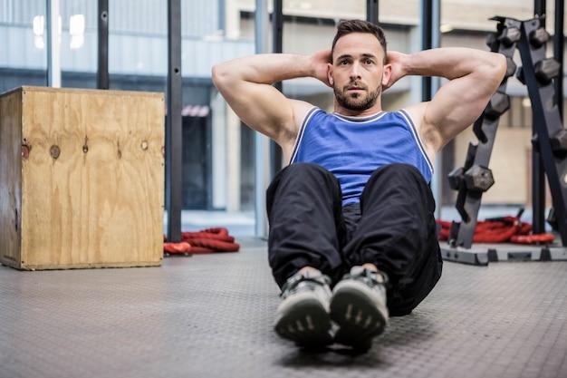 Muskulöser mann, der abdominal- krisen an der crossfit turnhalle tut