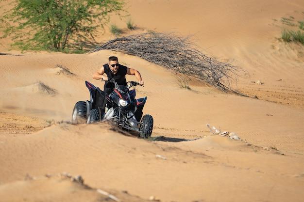 Muskulöser mann, der atv in der wüste reitet.