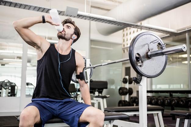 Muskulöser mann, der auf bank sitzt und an der turnhalle trinkt