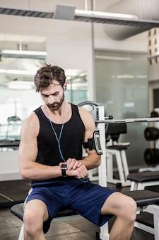 Muskulöser mann, der auf barbellbank sitzt und smartwatch an der turnhalle verwendet