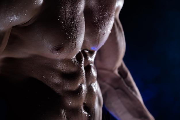 Muskulöser mann, der auf dem schwarz isolierte muskeln zeigt