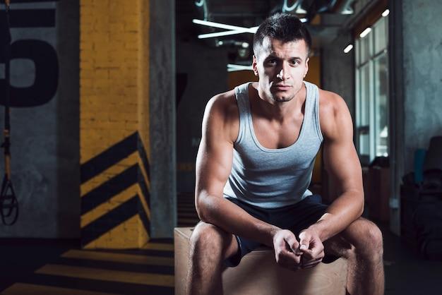 Muskulöser mann, der auf holzkiste im fitnessclub sitzt