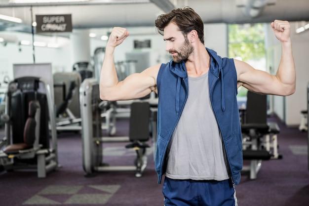 Muskulöser mann, der bizeps an der turnhalle zeigt