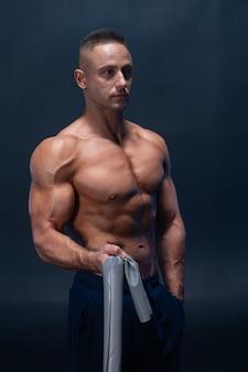 Muskulöser mann, der calisthenic übung mit kraftband isoliert tut.