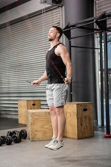 Muskulöser mann, der das seil an der crossfit turnhalle springt