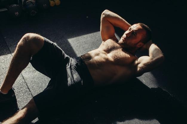 Muskulöser mann, der die sitzende übung ausübt
