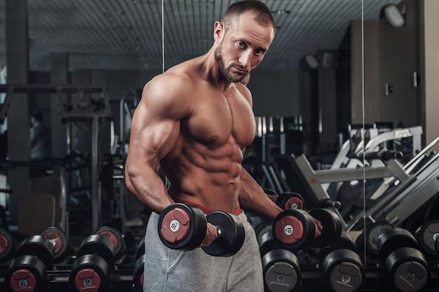 Muskulöser mann, der eine übung für bizeps tut