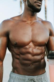 Muskulöser mann, der einen proteindrink trinkt
