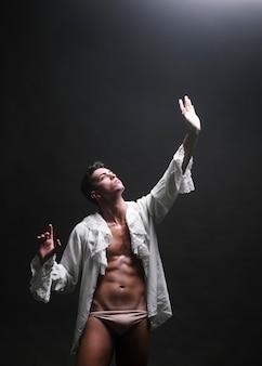Muskulöser mann, der heraus hand zum licht ausdehnt