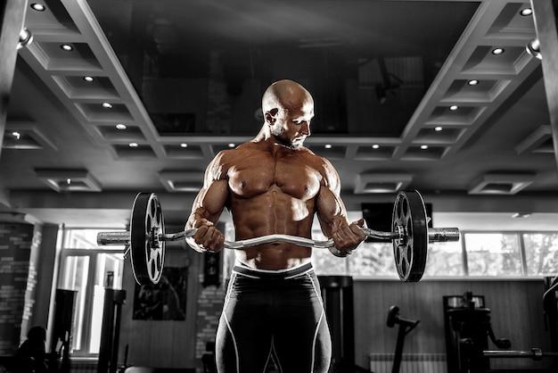Muskulöser mann, der im fitnessstudio trainiert, das übungen mit hanteln macht