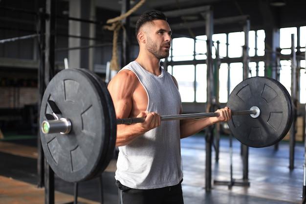Muskulöser mann, der im fitnessstudio trainiert und übungen mit der langhantel am bizeps macht.