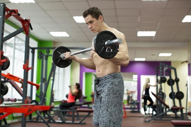 Muskulöser mann, der im fitnessstudio trainiert und übungen mit langhantel macht, starker männlicher nackter oberkörper