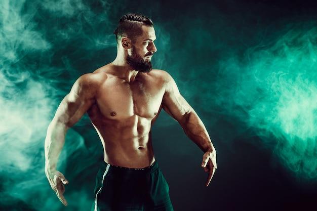 Muskulöser mann, der im studio aufwirft.