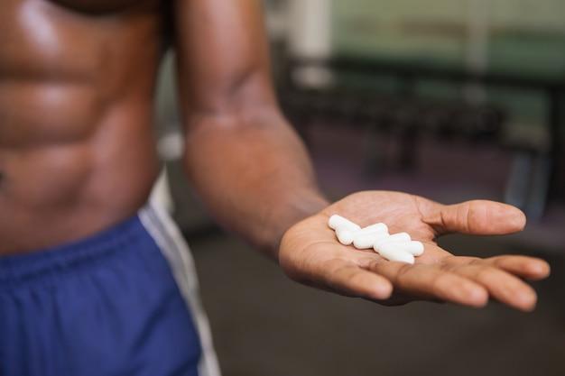 Muskulöser mann, der in der hand vitaminpillen hält