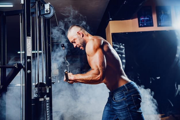 Muskulöser mann, der in der turnhalle tut übungen ausarbeitet
