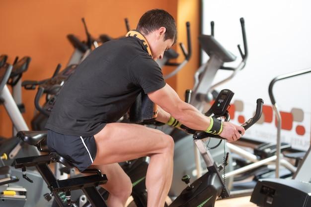 Muskulöser mann, der in die turnhalle, die beine trainierend radfahrenfahrräder des herz trainings und spinnen klasse radfährt.