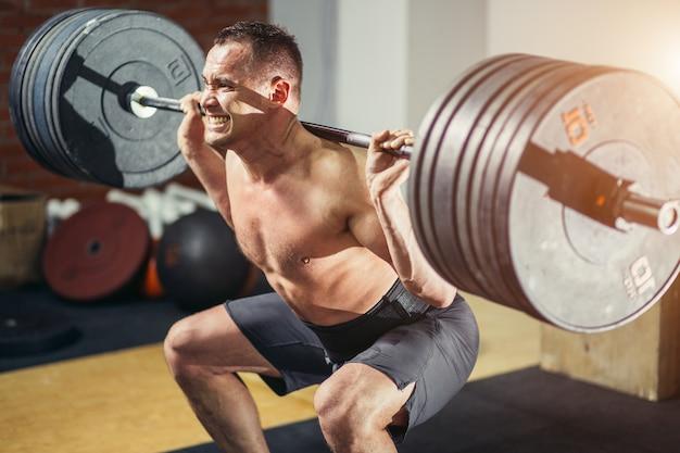 Muskulöser mann, der kniebeugen mit hanteln auf den schultern trainiert