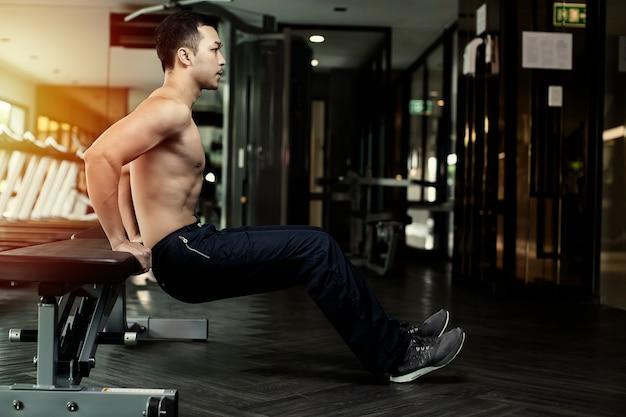 Muskulöser mann, der liegestütz auf stuhl tut