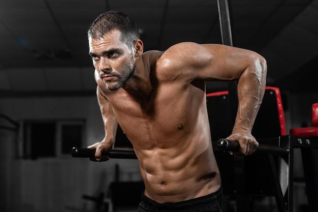 Muskulöser mann, der liegestütze auf stufenbarren in crossfit turnhalle tut