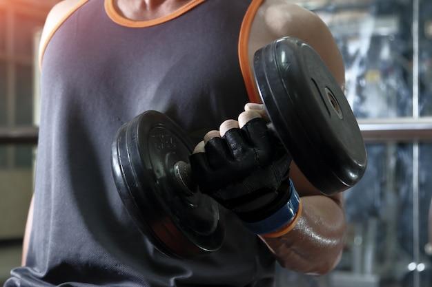 Muskulöser mann, der mit dummköpfen ausarbeitet.