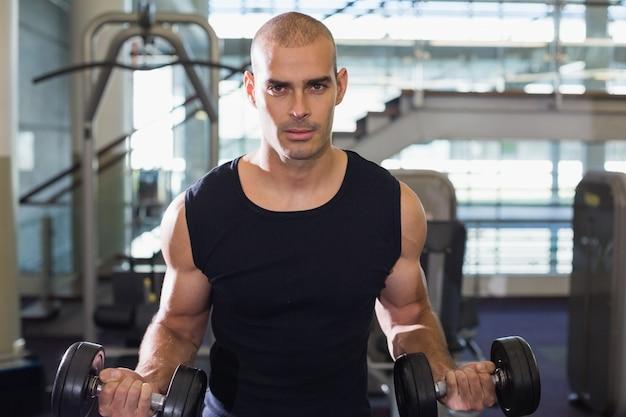 Muskulöser mann, der mit dummköpfen in der turnhalle trainiert