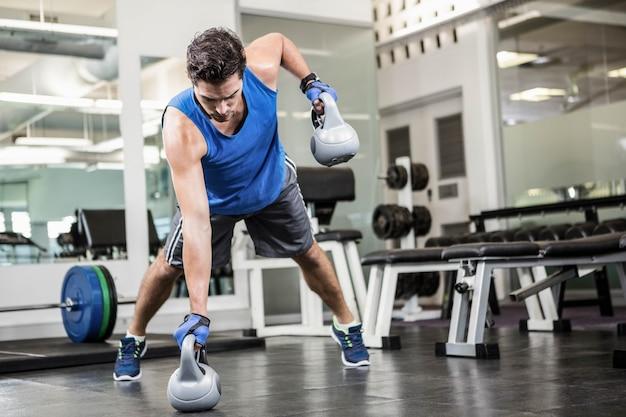 Muskulöser mann, der mit kettlebells an der turnhalle trainiert