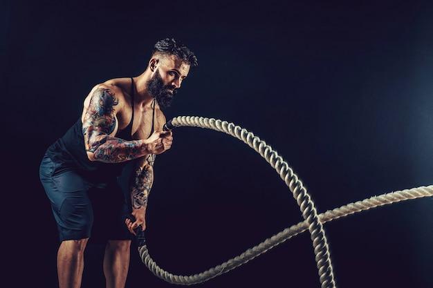 Muskulöser mann, der mit schwerem seilfoto des mannes mit nackter rumpfstärke und -motivation ausarbeitet