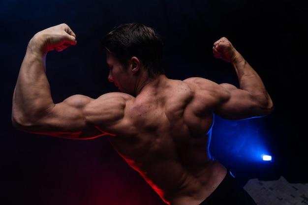 Muskulöser mann, der muskeln auf dem schwarzen hintergrund isoliert zeigt gesunder lebensstil