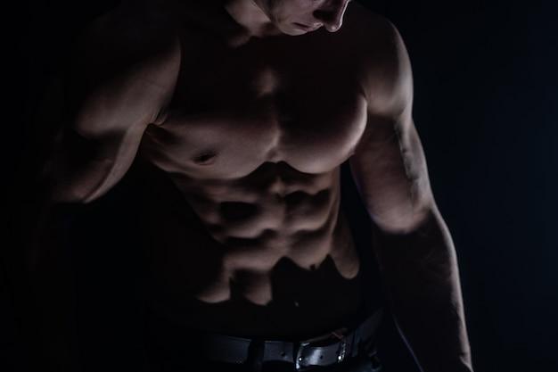 Muskulöser mann, der muskeln auf dem schwarzen hintergrund isoliert zeigt. konzept des gesunden lebensstils.