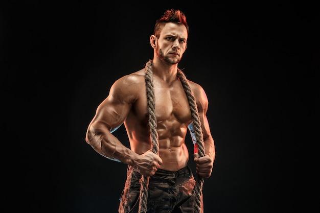 Muskulöser mann, der seil hält