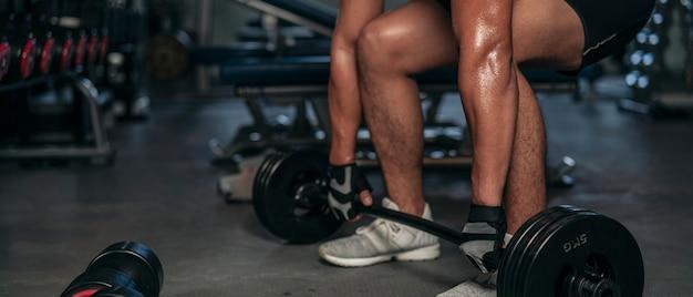 Muskulöser mann, der sportswear bodyweight lifting langhantel für bodybuilding-training im fitnessstudio trägt