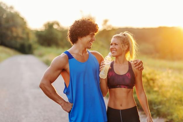 Muskulöser mann, der steht und seine freundin umarmt, während sie ihn ansieht und wasser trinkt. ländliches äußeres, sonniger sommertag.