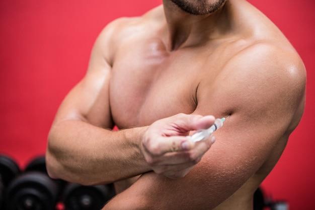 Muskulöser mann, der steroide einspritzt