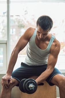 Muskulöser mann, der training mit dummköpfen tut