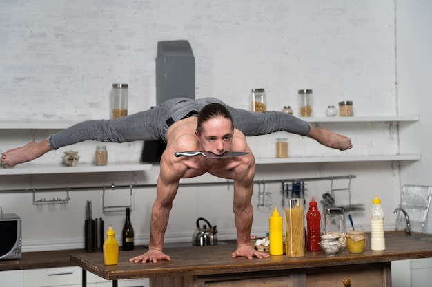 Muskulöser mann hält das gleichgewicht auf den händen in der küche und hält das messer im mund. konzeptkreativität in der küche und gesunder lebensstil.