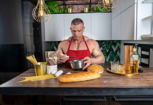 Muskulöser mann in der küche bereitet ein gericht vor