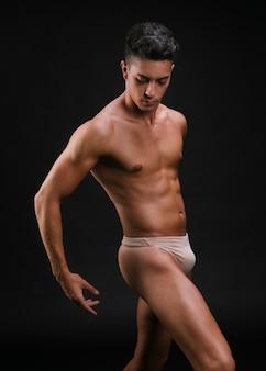 Muskulöser mann in der tanzenhaltung