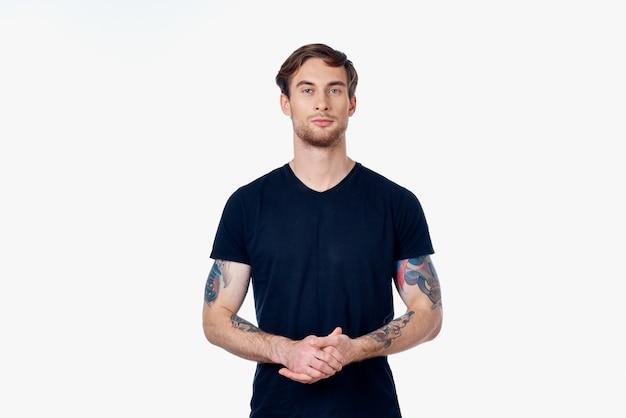 Muskulöser mann in einem blauen t-shirt mit tätowierungen auf den armen auf einem hellen hintergrund beschnittene ansicht