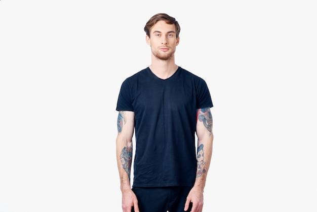Muskulöser mann in einem blauen t-shirt mit tätowierungen auf seinen armen
