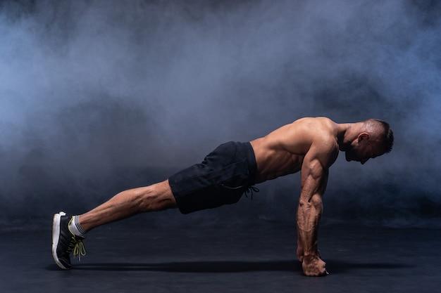 Muskulöser mann macht calisthenic-übungen isoliert auf schwarzem hintergrund